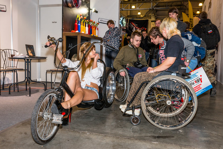 original bike: Winter 2015. Morning. Russia. Moscow. Crocus-Expo. Exhibition Motopark-2015 (BikePark-2015). The exhibition stand of the Thomi Felgen tuning studio. The girl on the original bike. Handmade. People in wheelchairs are looking the stand and they are talking  Editorial