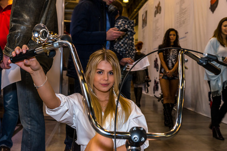 original bike: Winter 2015. Morning. Russia. Moscow. Crocus-Expo. Exhibition Motopark-2015 (BikePark-2015). The exhibition stand of the Thomi Felgen company. The girl on the original bike. Handmade. Editorial