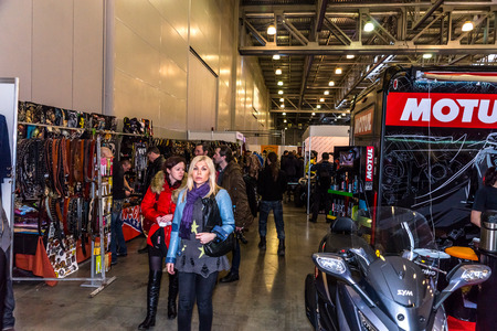 they are watching: Winter 2015. Morning. Russia. Moscow. Crocus-Expo. Exhibition Motopark-2015 (BikePark-2015). Visitors are walking through the exhibition. They are watching  stands of the exhibition. Editorial