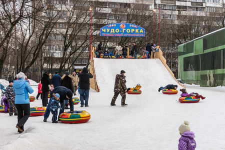 pancake week: Winter 2015. Day. Russia. Moscow. Maslenitsa (pancake week). The Celebration of Maslenitsa (pancake week). The people are sliding down the hill. Editorial