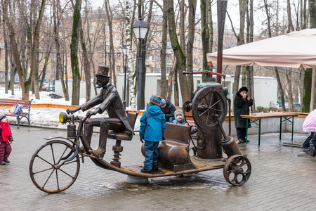 pancake week: Winter 2015. Day. Russia. Moscow. Maslenitsa (pancake week). The Celebration of Maslenitsa (pancake week). The children are viewing the sculpture in the form of an ancient car.