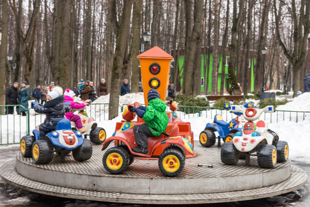 pancake week: Winter 2015. Day. Russia. Moscow. Maslenitsa (pancake week). The Celebration of Maslenitsa (pancake week). The people in the park of amusements. Small children ridind on the carousel.