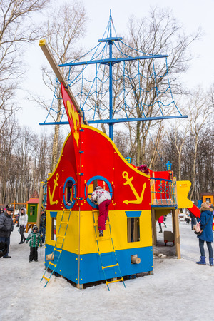 maslenitsa: Winter 2015. Day. Russia. Moscow. Maslenitsa (pancake week). The Celebration of Maslenitsa (pancake week). The playground for children in the Park. It is made in the form of a sailing ship. Children play on the Playground.