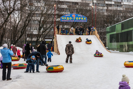 maslenitsa: Winter 2015. Day. Russia. Moscow. Maslenitsa (pancake week). The Celebration of Maslenitsa (pancake week). The people are sliding down the hill. Editorial