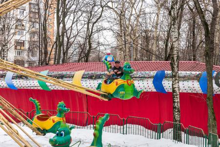 maslenitsa: Winter 2015. Day. Russia. Moscow. Maslenitsa (pancake week). The Celebration of Maslenitsa (pancake week). The people in the park of amusements. Small children ridind on the carousel.