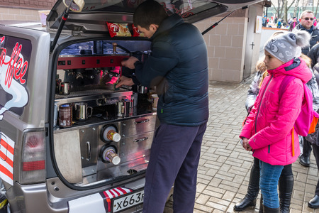 pancake week: Winter 2015. Day. Russia. Moscow. Maslenitsa (pancake week). The Celebration of Maslenitsa (pancake week). The mobile cafe. The barista prepares coffee for the young client.