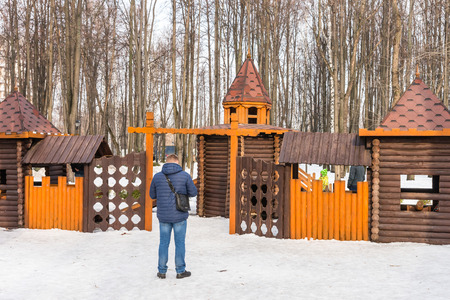 maslenitsa: Winter 2015. Day. Russia. Moscow. Maslenitsa (pancake week). The Celebration of Maslenitsa (pancake week). The man is looking for his child on the Playground for children, built in form of the castle. Editorial