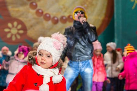 maslenitsa: Winter 2015. Day. Russia. Moscow. Maslenitsa (pancake week). The Celebration of Maslenitsa (pancake week). The concert in honor of the Holiday. The performance of Michael Grebenshchikov. Children dancing on scene with Michael Grebenshikov.