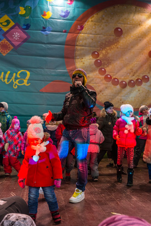 pancake week: Winter 2015. Day. Russia. Moscow. Maslenitsa (pancake week). The Celebration of Maslenitsa (pancake week). The concert in honor of the Holiday. The performance of Michael Grebenshchikov. Children dancing on scene with Michael Grebenshikov.