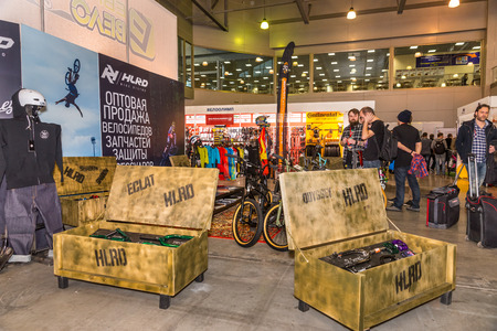 they are watching: Winter 2015. Russia. Moscow. The exhibition Bikepark-2015. General view. People are walking at the exhibition. They are watching the stands with bicycles, equipment and clothes.