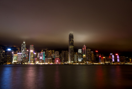 Hong Kong harbour at night.  Taken from the Kowloon side facing over the Victoria harbour on January 8th, 7:45pm.  Low level cloud tips the tallest skyscraper on the island and bounces light back down. Editorial
