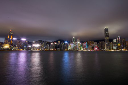 Hong Kong harbour at night.  Taken from the Kowloon side facing over the Victoria harbour on January 8th, 7:45pm.  Low level cloud tips the tallest skyscraper on the island and bounces light back down. This shot embraces most of the key buildings along th Editorial