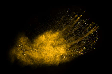 Freeze motion of yellow dust explosion isolated on black background.