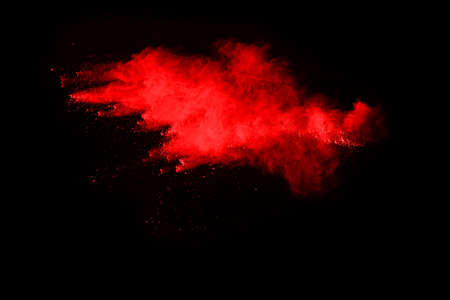 abstract red powder explosion on black background.abstract red powder splatted on black background. Freeze motion of red powder exploding.