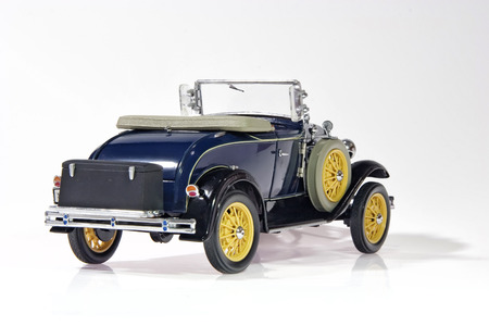 A scale model of vintage car in 1930s. White background.