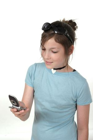 Cute young teenage girl standing up and talking on a cellphone; shot on white Stock Photo