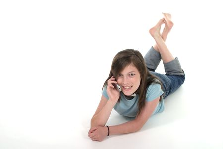 Cute young teenage girl sitting on the floor and talking on a cellphone; shot on white
