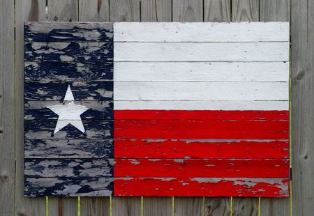 Texas flag made from painted wood slats on a wood fence