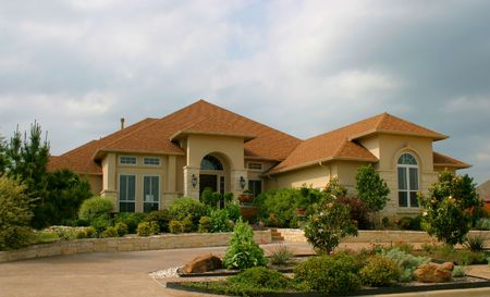 modern brick and stucco house with extensive landscaping and plantings in front Stock Photo - 441045