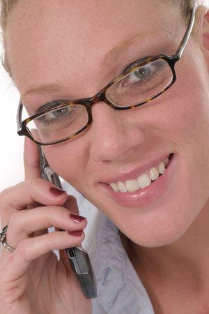 Closeup van aantrekkelijke glimlachend zakelijke vrouw praten over mobiel en het dragen van een bril