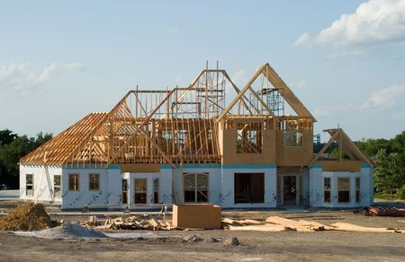 Very large suburban house under construction.  Roof joists still visible.  Construction crews have begun adding wall insulation board.