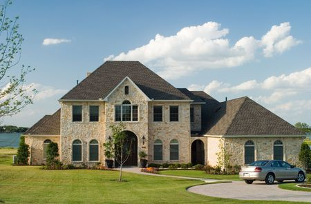 Very large and beautiful stone and brick house on a small lake with generic car in front circle drive and white puffy clouds in the sky.