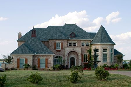 Huge brick modern French provencial style house with ornate fountain and beautiful landscaping on small lake. photo