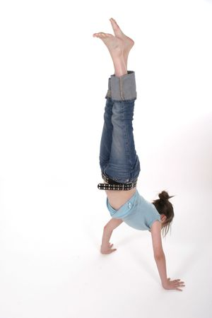 Young pre teen girl standing on her head or doing a handstand.