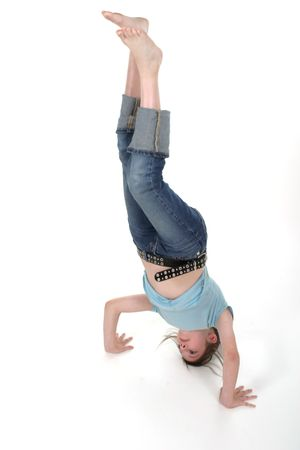 pre teen: Young pre teen girl standing on her head or doing a handstand.