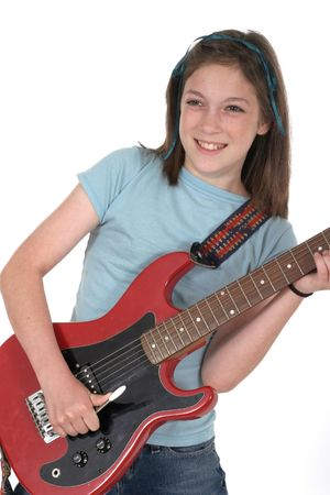 Young pre teen girl playing a red electric guitar. Stock Photo