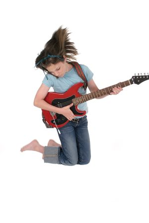 Young pre teen girl jumping up and playing a red electric guitar. Stock Photo