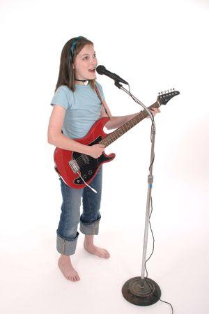Los j�venes pre adolescentes ni�a cantando y tocando guitarra el�ctrica roja.  Foto de archivo - 449267
