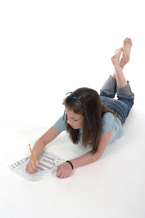 scribbling: Young girl with blue ribbon in her hair drawing and scribbling on paper on the floor.