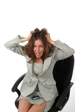 Frustrated executive business woman with a troubled expression sitting in her office chair pulling her hair out. photo