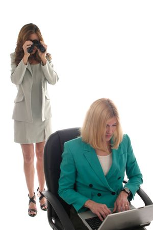 Business woman using binoculars to spy on another business woman working on laptop computer. Focus is on woman with binoculars in background. Stock Photo