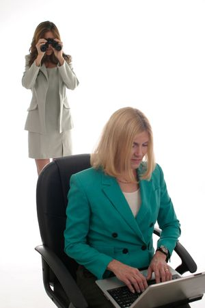 corporate espionage: Business woman using binoculars to spy on another business woman working on laptop computer. Stock Photo