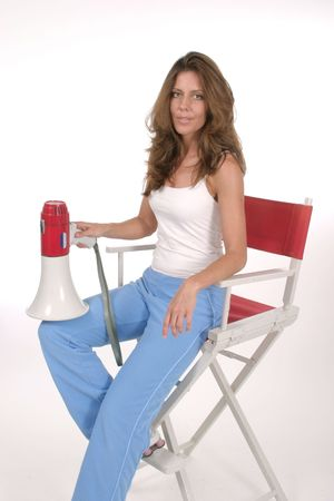 Beautiful woman sitting in red directors chair holding a megaphone.  Portrait orientation.  Shot on white.