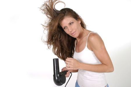 Beautiful brunette woman drying her hair with a blow dryer. Archivio Fotografico