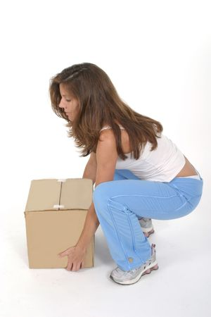Beautiful attractive woman squatting and lifting a small plain brown box with her knees bent. Stock Photo