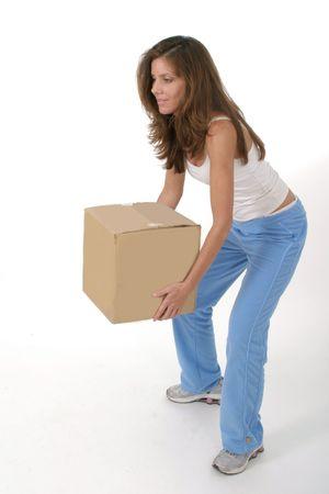 knees bent: Donna attraente bella che accovaccia e che alza una piccola scatola marrone normale con le sue ginocchia piegate.