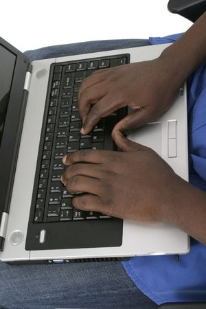 Black African American hands typing on laptop computer keyboard. photo