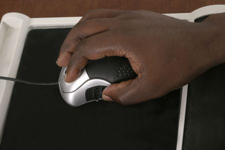 Black African American hands manipulating a computer mouse on a mousepad.  Landscape orientation. photo