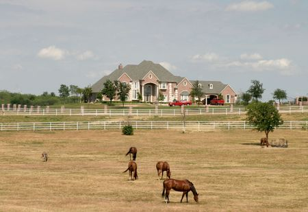 Sprawling modern estate in rural setting with obiligatory pick-up trucks in the driveway and horses in pasture in the foreground.  photo