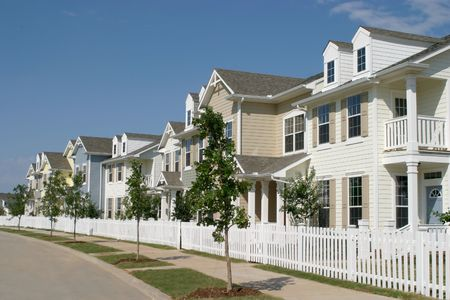 Long row of suburban townhouses with a white picket fence in front.    photo