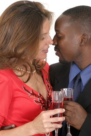 Handsome man and beautiful woman embracing and about to kiss while celebrating a romantic occasion with a bottle of champagne or sparking wine. Standard-Bild