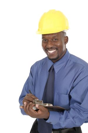 Smiling architect, engineer, or supervisor in yellow hardhat holding a clipboard and pen. Stock Photo