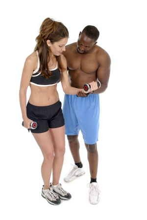 Woman in fitness workout clothing is getting help from a male personal trainer in using hand weights.  Isolated shot on white. Stock Photo