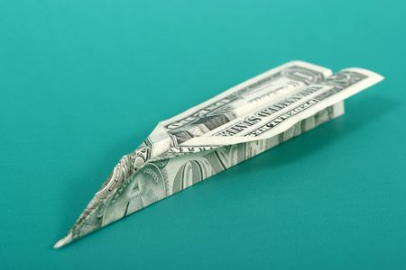 US dollar bill folded into a paper airplane on a green background. Stock Photo