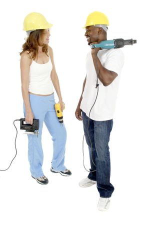 Attractive working woman and man couple in hardhats holding powertools. photo