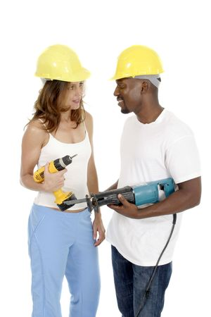 Attractive working woman and man in hardhats holding powertools. photo